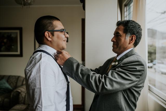 papa del novio ayudando a vestir al novio