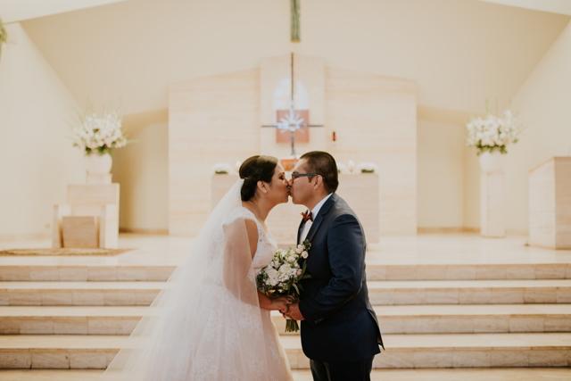 Novios en el altar dándose su primer beso de casados