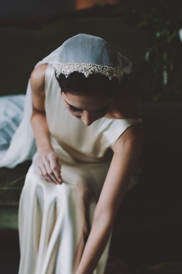 novia tocandose los zapatos y con un velo estilo juliet cap con aplicaciones de perlas