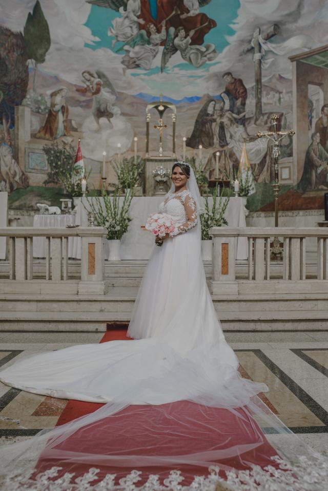 Novia en la iglesia mostrando su vestido.
