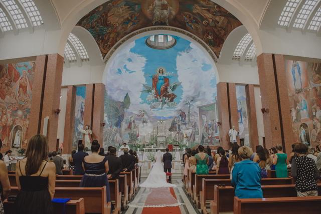 Novios en la ceremonia religiosa, arrodillados ante el altar