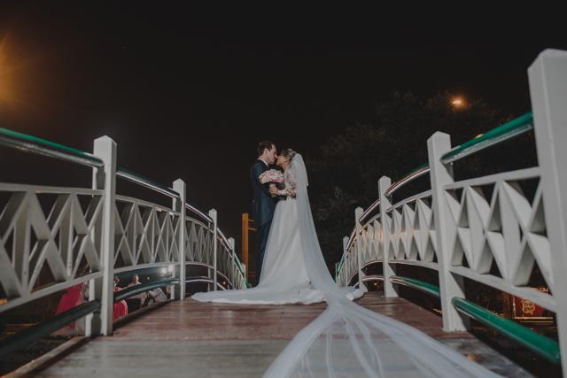 Novios arriba del puente, mostrando la cola del velo de la novia