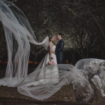 Novios en el jardín de noche, mostrando la cola de la novia de 7 metros