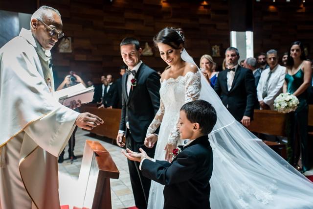 hijo entregando los aros al sacerdote